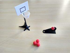 se muestra un mini juego de baloncesto impreso en una impresora 3D